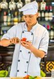 HANOI, VIETNAME - 16 DE DEZEMBRO DE 2016: Um cozinheiro corta um tomate em uma placa de corte vertical Imagens de Stock Royalty Free