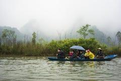 Hanoi, Vietname - 23 de fevereiro de 2014: Os turistas no barco de enfileiramento na maneira ao pagode de Huong no festival tempe fotos de stock