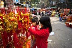 Hanoi, Vietname - 26 de janeiro de 2017: Crianças que veem a decoração pelo ano novo lunar vietnamiano na rua de Hang Ma Fotos de Stock Royalty Free