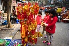 Hanoi, Vietname - 26 de janeiro de 2017: Crianças que veem a decoração pelo ano novo lunar vietnamiano na rua de Hang Ma Imagem de Stock Royalty Free