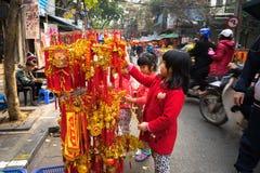 Hanoi, Vietname - 26 de janeiro de 2017: Crianças que veem a decoração pelo ano novo lunar vietnamiano na rua de Hang Ma Fotografia de Stock Royalty Free