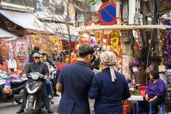 Hanoi, Vietname - 26 de janeiro de 2017: Uma mãe e seu filho tomam uma decoração e uma flor de compra da caminhada pelo ano novo  Imagens de Stock