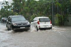 Hanoi, Vietname - 17 de julho de 2017: O carro espirra através de uma grande poça na rua inundada após a chuva pesada em Minh Kha Foto de Stock