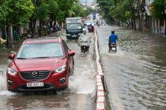 Hanoi, Vietname - 17 de julho de 2017: O carro espirra através de uma grande poça na rua inundada após a chuva pesada em Minh Kha Imagens de Stock Royalty Free