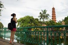 Hanoi, Vietname - 12 de junho de 2016: Mulher vietnamiana que reza de uma distância fora de Tran Quoc, o templo o mais velho em H Imagens de Stock