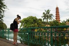 Hanoi, Vietname - 12 de junho de 2016: Mulher vietnamiana que reza de uma distância fora de Tran Quoc, o templo o mais velho em H Fotos de Stock