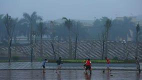 Hanoi, Vietname - 13 de março de 2015: Os meninos estão jogando o futebol (futebol) sob a chuva video estoque