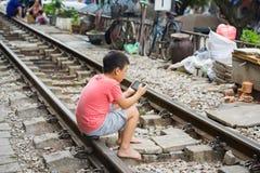 Hanoi, Vietname - 8 de novembro de 2015: O jogo de crianças em nenhumas barreiras treina a estrada de ferro em Hanoi Fotografia de Stock
