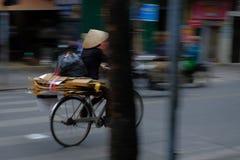 Hanoi/Vietname, 05/11/2017: Mulher vietnamiana na bicicleta com o chapéu tradicional do arroz em uma estrada hética ocupada com p foto de stock royalty free