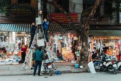 Hanoi, Wietnam, 12 20 18: Życie w ulicie w Hanoi Elektryk próba załatwiać niektóre problem z elektrycznością fotografia stock