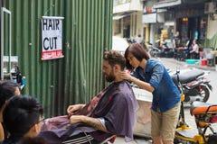 Hanoi Wietnam, Apr, - 5, 2015: Niezidentyfikowanego żeńskiego fryzjera męskiego rżnięty włosy na ulicie w Hanoi, Wietnam Fryzjer  Fotografia Stock