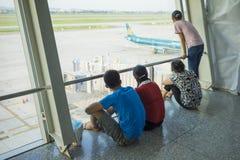 Hanoi Wietnam, Lipiec, - 12, 2015: Azjatycki klienta spojrzenie przy samolotem podczas gdy czekający wsiadający czas przy Noi Bai Zdjęcie Stock