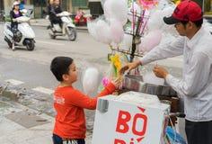 Hanoi Wietnam, Mar, - 15, 2015: Chłopiec kupuje bawełnianego cukierku floss od sprzedawcy na Ly Tajlandzkim ulica Zdjęcia Royalty Free