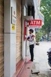 Hanoi Wietnam, Mar, - 15, 2015: Mężczyzna jest ubranym hełm wycofuje pieniądze od Techcombank ATM na Ly Tajlandzkim ulica Obraz Stock
