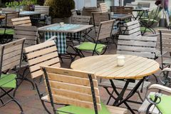 Hanover, Nedersaksen, Duitsland, 19 Mei, 2018: Onbezette stoelen en lijsten in een tuinrestaurant met lijstbenen en stoelbenen m Stock Fotografie