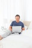 hans bärbar dator som ser mannen Arkivbild