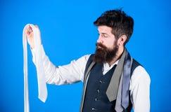 Hans garderob framlägger hans stilavkänning Skäggig man som väljer en slips från hans garderob Stilfulla mäns garderob för fotografering för bildbyråer