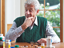 hans looks man den fundersama pensionären för många pills Royaltyfri Foto