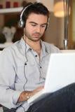 hans lyssnande manmusik till Arkivbild