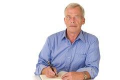hans manminnespensionär skriver Royaltyfri Foto
