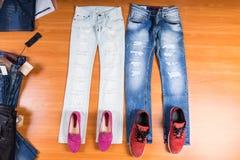 Hans och hennes jeans som läggas med skor Arkivfoto