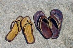 Hans och hennes sandaler för flipmisslyckande på den sandiga stranden Arkivfoton