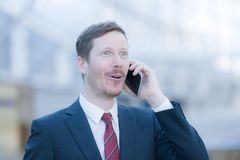 Hansdome man on the phone is happy and hearing good news. Surprised by a good news on the phone, a business man is making a phone call, wearing a dark blue Royalty Free Stock Photo