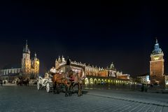 Hansom cab at night on Old Town square in Krakow. KRAKOW, POLAND - JUNE 11: Horse drawn carriages at night with guides in front of the St. Mary's Basilica on stock images
