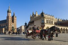 Hansom cab on Old Town square in Krakow, Poland. KRAKOW, POLAND - JUNE 11: Horse drawn carriages at night with guides in front of the St. Mary's Basilica on royalty free stock photography