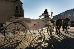 Hansom cab woman on Old Town square in Krakow. KRAKOW, POLAND - MARCH 13: Hansom cab woman waiting to whisk tourists around the beautiful city of Krakow on March stock photos