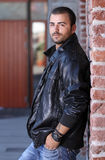 Hansom man in thick leather jacket. Near a vintage brick wall royalty free stock photo