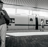 Hansom man waiting for the train in Germany. MANNHEIM, GERMANY - AUG 8, 2017: Black and white image of beautiful German man waiting at the train station platform royalty free stock photo