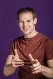 Hansom young man. Hansom young confidant man pointing over a purple background stock photos