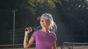 hansome妇女画象有网球拍的在网球制服走室外 影视素材