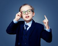 Hansome boy wearing glasses and a black suit. Isolated against studio background Royalty Free Stock Photo