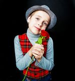 Hansome boy  with rose in his hands. Hansome boy wearing a hat and a vest with rose in his hands, isolated against black studio background Royalty Free Stock Photo