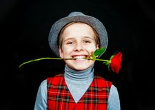 Hansome boy   with rose in his teeth. Hansome boy wearing a hat and a vest with rose in his teeth, isolated against black studio background Royalty Free Stock Photos