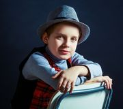 Hansome boy wearing a hat and a vest sitting on the chair. Isolated against black studio background Royalty Free Stock Photos