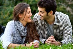 Hansome couple laying on grass outdoors. Stock Photography