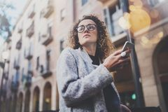 Hansome girl hipster wearing glasses searching information in mobile network by smart phone, during walk in european. City. Bokeh and flares effects on blurred Royalty Free Stock Photos