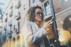 Hansome girl hipster wearing glasses searching information in mobile network by smart phone, during walk in european. City. Bokeh and flares effects on blurred Stock Photos