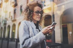 Hansome girl hipster wearing glasses searching information in mobile network by smart phone, during walk in european. City. Bokeh and flares effects on blurred Royalty Free Stock Images
