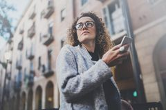 Hansome girl hipster wearing glasses searching information in mobile network by smart phone, during walk in european. City. Bokeh and flares effects on blurred Stock Images