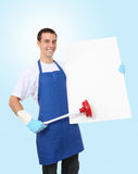 Hansome Man Cleaner with Sign. A handsome young man with cleaning supplies and sign royalty free stock photo