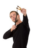Hansome man concentrated aiming a slingshot Royalty Free Stock Photos