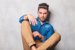 Hansome man in denim shirt sitting in studio legs crossed Stock Photo