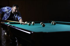 Hansome man playing billiards alone Royalty Free Stock Image