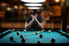 Hansome man playing billiards alone Royalty Free Stock Photos