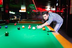 Hansome man playing pool in bar alone. Aiming Royalty Free Stock Photos