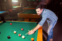Hansome man playing pool in bar alone. Aiming Royalty Free Stock Image